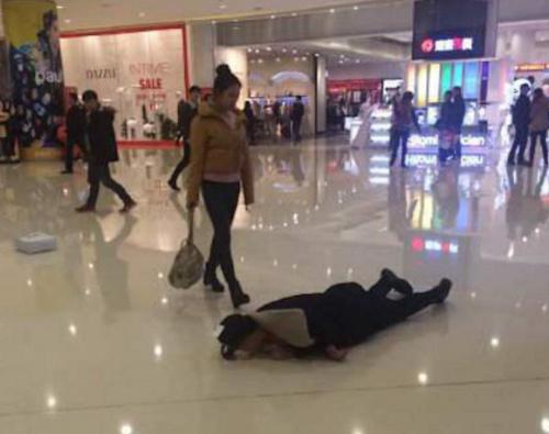 Chàng trai lăn lộn trên sàn nhà sau khi cãi nhau với bạn gái. Ảnh: Weibo.